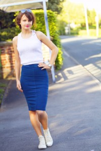White racer back knit top worn with denim midi skirt and converse
