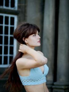 UK teen fashion blogger with long brunette hair wearing blue crochet bralet