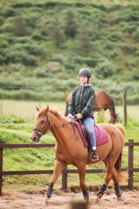 Teenager riding chestnut horse at Glenbar trekking centre Argyll Scotland