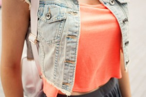 Bleached denim gilet from Top Shop worn with coral crop top