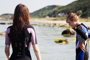 Teenagers wearing wetsuits on Muasdale beach Argyll Scotland
