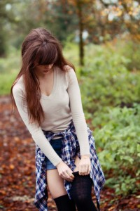 Teen blogger wearing denim shorts and plaid shirt