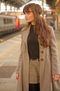 Teen blogger wearing check shorts photographed at Preston Railway Station