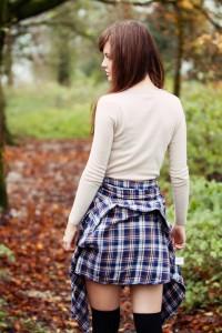 Teen wearing plaid shirt knotted around waist