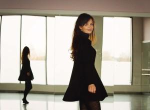 Short black swing dress worn with stripey tights