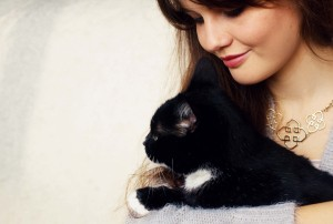 Teen lifestyle blogger cuddling black and white cat
