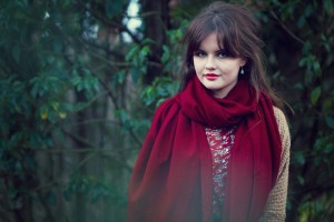 Rich red scarf photographed against leafy green background