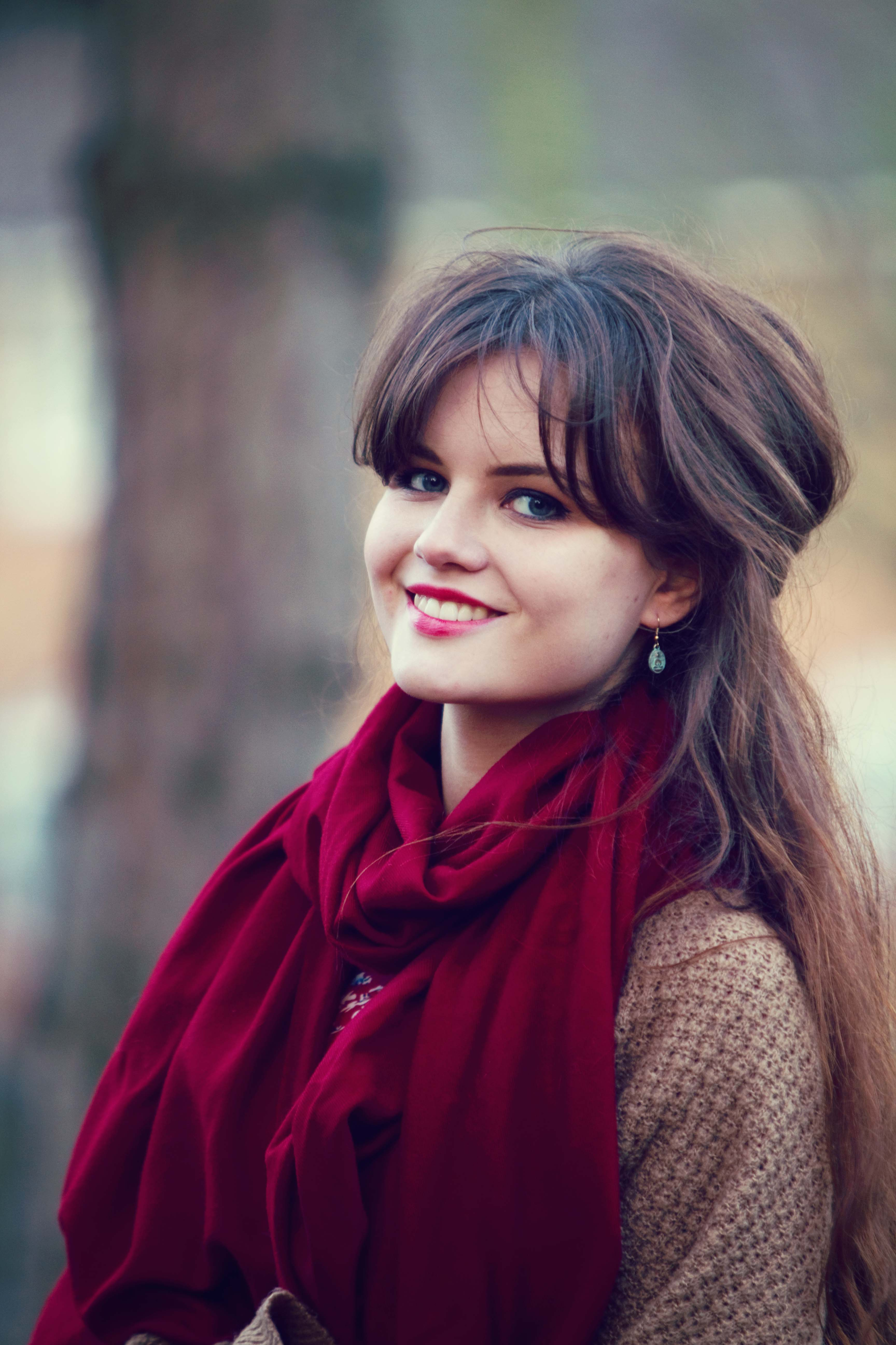 Very smiley brunette wearing ruby red scarf