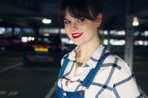 Smiling UK teen wearing plaid shirt and dungarees