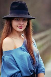 Brunette blogger wearing black fedora hat