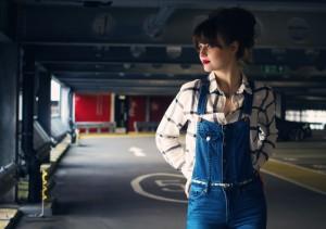Plaid shirt worn with denim dungarees. Photographed at Preston railway station