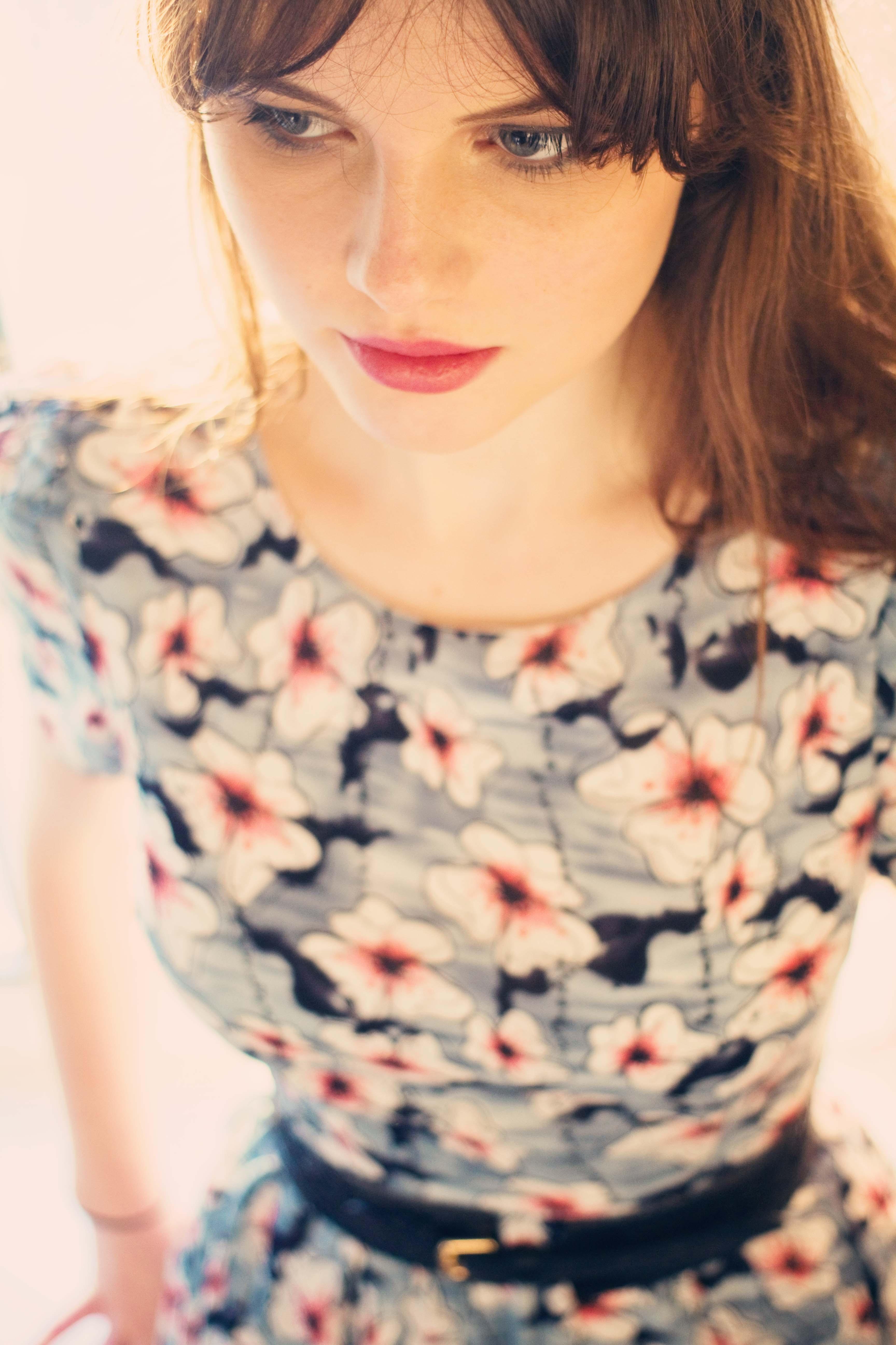 Teen blogger wearing grey floral dress and plum lipstick