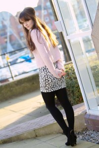 Teen looking back over shoulder wearing pale pink rib sweater