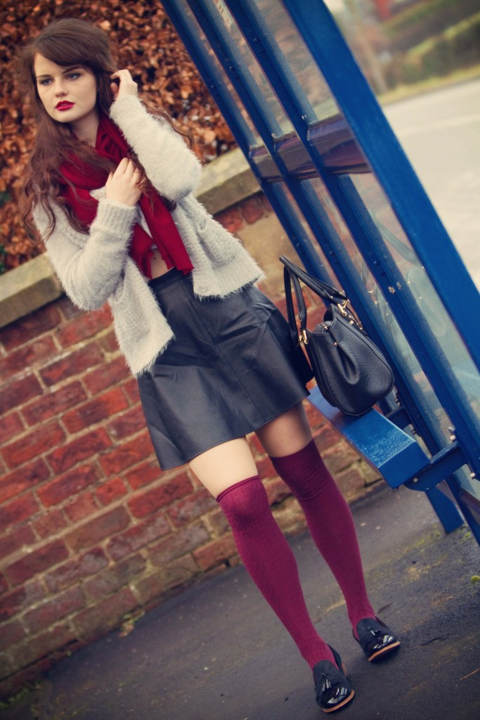 Brunette girl waiting at bus stop on rainy day