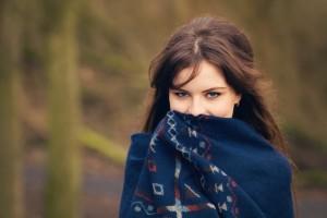Brunette teen hiding face behind shawl