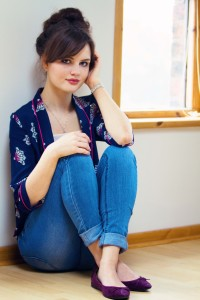 Brunette wearing Tollied Dolly jacket and blue cropped jeans