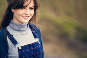 Smiling teen wearing grey roll neck and navy pinafore