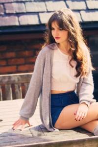 Teen girl wearing denim shorts and grey cardigan