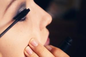 Teen girl applying mascara to smokey eye
