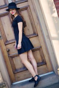 Teen girl wearing black dress and Fedora hat shot in front of wooden door