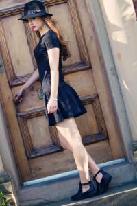 Teen girl opening wooden door. Black dress and black Fedora