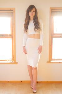 Teen girl portrait shot between 2 windows wearing all cream outfit