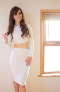 Teen girl with brunette wavy hair wearing cream bodycon outfit