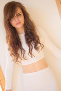 Teen girl wearing cream body con outfit. Messy brunette hair