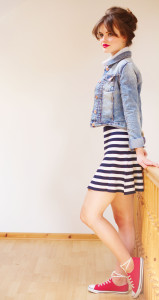 Teen girl wearing denim jacket, flippy skirt and red lac up pumps