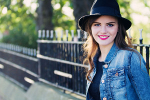 Teen blogger photographed against black railings wearing black fedora hat and denim jacket