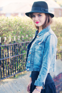 Teen girl wearing denim jacket black dress and black Fedora hat