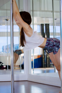 Teen girl having first pole dance lesson