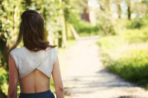 Cross back handknit top from Purl Soho pattern. Girl walking along woodland path