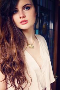 Brunette girl wearing chiffon cream playsuit