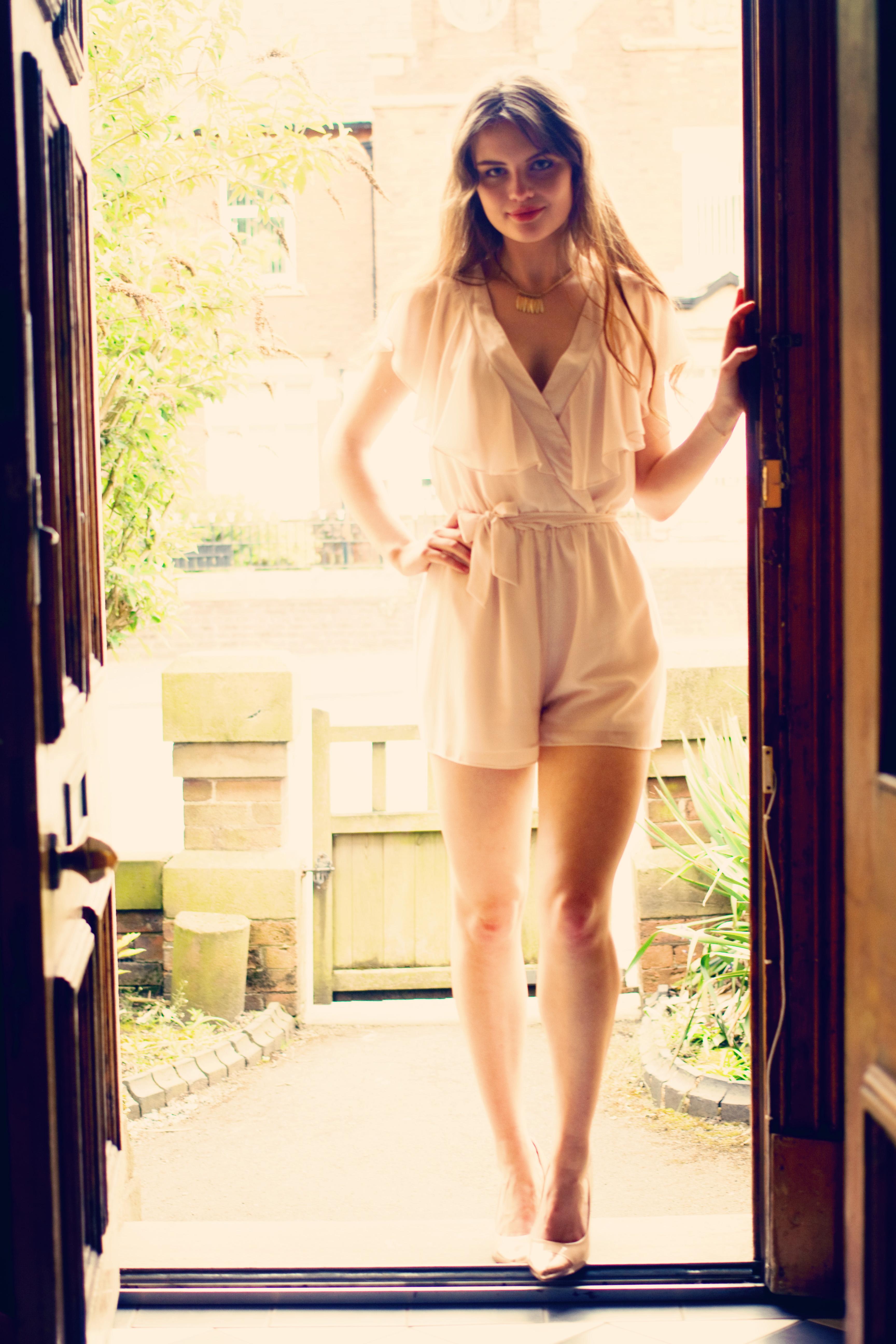 Teen photographed in doorway wearing cream playsuit