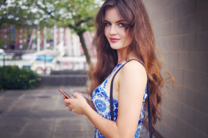 Teen wearing blue and white dress using Sony phone