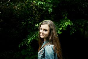 Teen blogger portrait shot against leafy green background