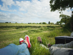 teen couple lying in grass on sunny day