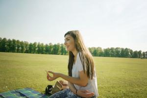 Brunette smiling girl sitting on lawn