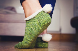 Green and white handknit socks with pom pom detail