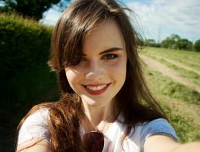 Teen girl walking in field on sunny day