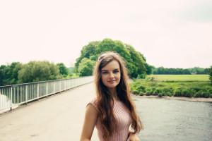 Teen girl photographed on river bridge