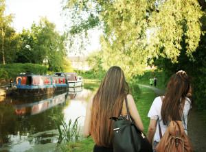 Brunette teens walking along canal