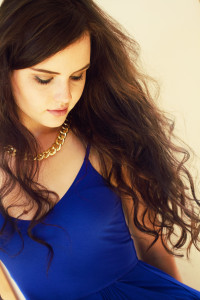 Teen with long brunette hair wearing strappy royal blue dress