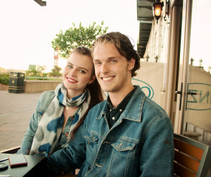 Young couple sat at table outside cafe