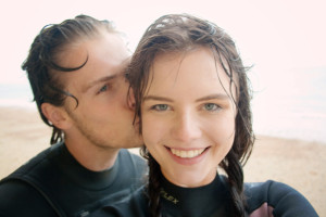 Cute young teen couple with wet hair and wearing wetsuits