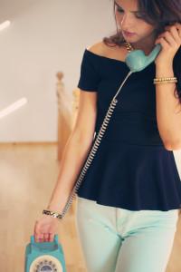 Teen girl holding handset of vintage telephone