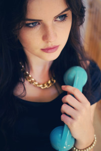 Teen girl looking thoughtfully whilst using vintage telephone