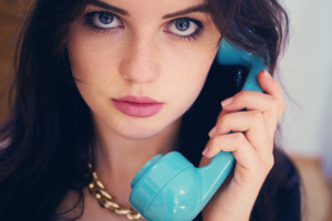 Teen girl using vintage style telephone