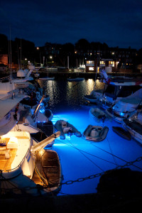 Boats in Weymouth harbour lit from underwater lighting